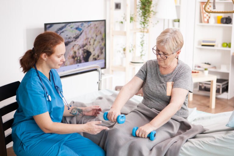 Health visitor helping old woman in nursing home to do her physiotherapy using dumbbells.