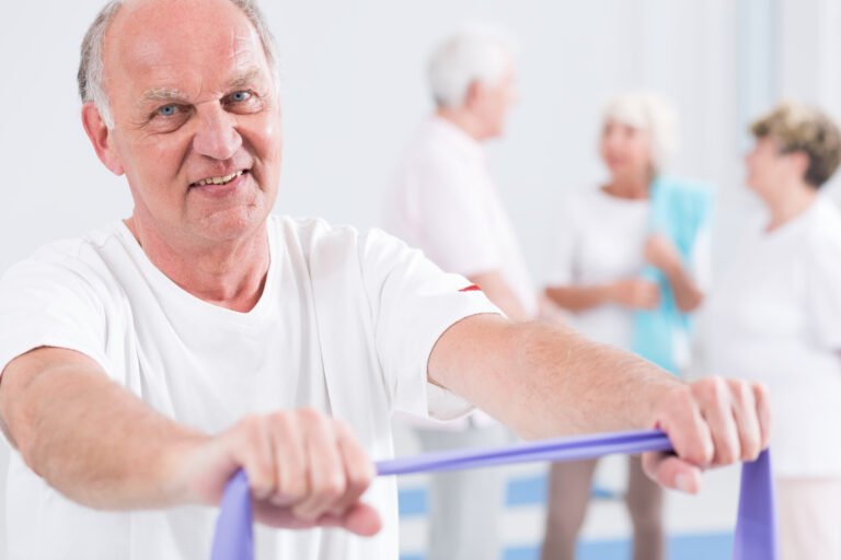 Smiling old man exercising with exercise band